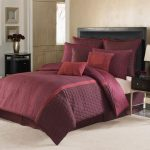 Luxurious Marroon Bedding Set With Bold And Tender Pillows And Quilt In Creamy Bedroom Aside Black Wooden Side Table On Creamy Floor