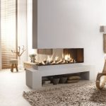 luxurious white three sided fireplace design with glass enclosure aside creamy area rug and curved rattan relaxing chair with floor lamp and wooden draped window