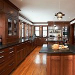 luxurious wooden kitchen design with wooden cabinetry with black soapstone countertop with island beneath chandelier