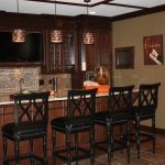 marble table bar with black barstools a counter with sink and faucet plus mosaic tiles backsplash floating cabinets in dark brown staining three pendant lighting units
