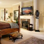 master bedroom ideas with basket weave carpet and four polster bed and fireplace combined with tv on fire mantel plus pretty table lamp
