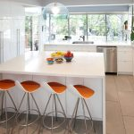 minimalist coner kitchen design with simple white cabinetry with glass windows and large island with storage with unique white orange stools beneath glass pendant