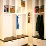 minimalist mudroom storage units in white with shelves for books and hanging jacket and wooden laminate floor