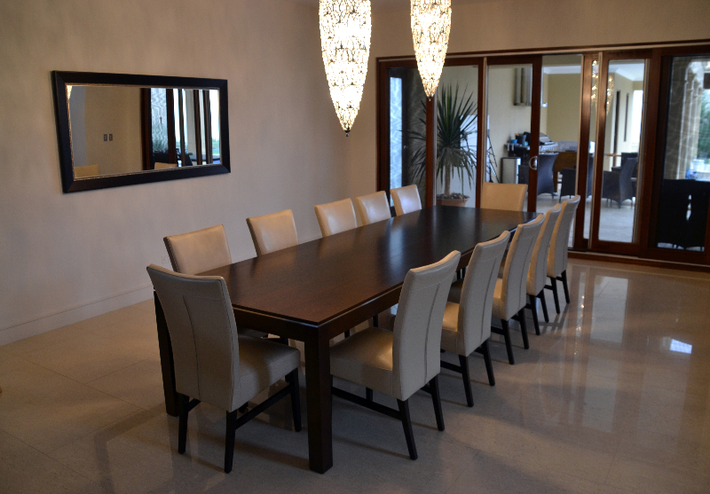 dining room with long wooden dining table and gray leather dining