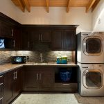 modern and luxurious laundry room design with black cabinetry with gray backsplash with natural wooden ceiling idea with washer and dryer
