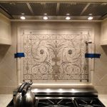 modern and sophisticated cooktop design with cettle beneath spanish tile backsplash around creamy wall between upper storage
