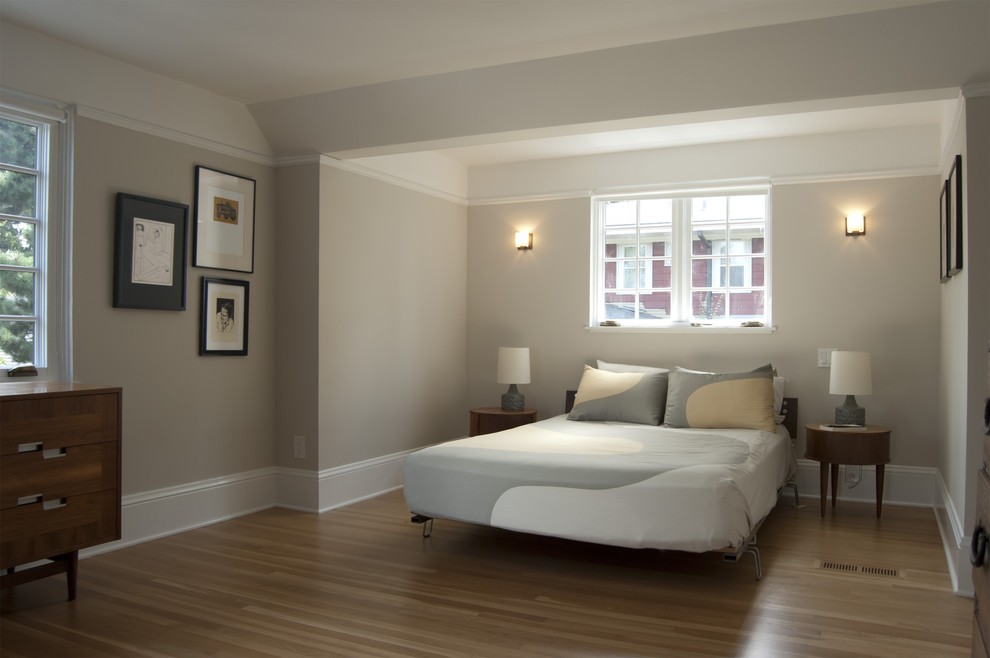 modern bedroom with baseboard styles in white together with comfy bedding and round nightstand plus table lamp and wooden flooring