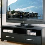 modern black low profile media console with media storage and drawers plus big screen TV and soft beige rug on laminate flooring