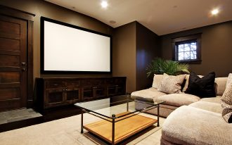 modern wooden low profile media console in home theater living room with sectional sofa and cushions plus glass coffee table and beige rug plus big screen and brown wall scheme