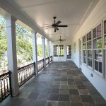 natural stones tiles floors for large porch fabricated metal railings for porch some concrete pillars in white two units of outdoor ceiling fans with lamps
