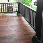 natural tone colors wood planks floors for front porch and black painted vertical wood railing systems