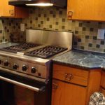 natural wooden cabinetry with gray soapstone countertop with mosaic casa antica tile with modern grill