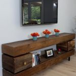 old fashioned wood low profile media console with drawers and TV on wall combined with book and beautiful lily vases and wooden floors