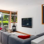 opened sliding glass door in environment friendly home a sectional sofa in grey color floating flat TV wood floors