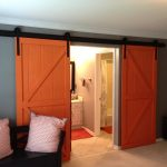 Orange Barn Door Design With Black Metal Sliding Model In Large Style In Gray Wall Aside Black Chairs With White Cushions