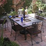 outdoor dining space design with rectangle table with metal chairs idea with pinkish tile flooring over concrete design aside garden
