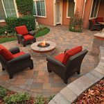 outdoor patio design with black rattan armchairs with red bolster and round in ground fire pit