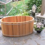 oval wooden japanese soaking tub small for outdoor bathroom with beautiful garden and natural stone flooring