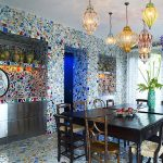 playful dining room design with wooden dining table with wooden chairs beneath colorful pendants with colorful mosaic casa antica tile with modern cabinetry