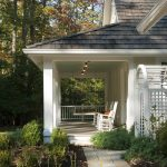 porch with a set of wood chairs in white paint color and white paint wood railings