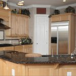 price of granite countertops for traditional cream wooden kitchen cabinets and sink plus tile backsplash and pendant lamps and greenery on top plus sink