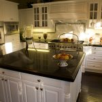 price of granite countertops in black with wooden cabinets and impressive backsplash plus wooden floor and built in oven