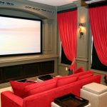 private home theater with bright red sofas red window curtains big screen a pair of lighting fixtures mounted on wall