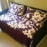 queen size daybed frame with trundle and marron bedding set with pretty motif and pillows next to windows with curtains