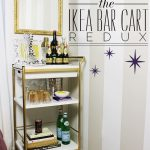 redux gold bar carts ikea with liqours and straws and cocktail glasses and books plus gold frame mirror on wallpaper wall and wooden laminating floor