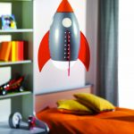 rocket airplane light fixture in kid bedroom with comfy bedding set and pillows plus wooden shelves