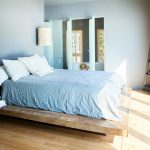 rustic elevated platform bed in wooden combined with blue bedding and blue wall paint plus pendant lamps and glass door plus corner bookshelf