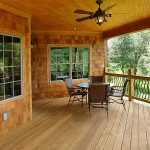 rustic ranch home with  porch a set of rattan chairs with metal structure round black table  vertical metal railings with wood main structure log pillars an outdoor ceiling fan with lamp wood planks floors