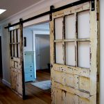 rustic white metal barn door design with plaid accent and black metal sliding rod upon bamboo laminated flooring on white wall