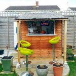 sheds turned into homes mini bar in backyard with green bar chairs and wooden wall plus plant pot and green grass