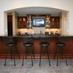 simple bar for basement with black painted barstools darker brown bar table mounted TV screen framed with floating cabinets with glass door