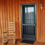 simple black screen door with glass panel darker stained wood planks wall system  wood planks floors a wood rocking chair a gold tone wall lighting fixture a black rubber mat for entry door