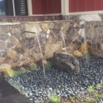simple-cool-good-awesome-water-feature-for-home-with-three-pipes-design-over-rock-wall-and-has-many-rock-black-rocks