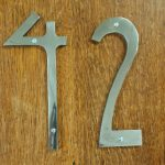 simple silver art deco house numbers in wooden entry door as an address home number