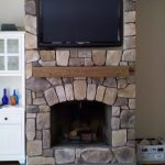 simple stone fireplace idea with cedar accent above the arched style with television set upon brown glossy flooring idea