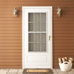 simple white screen door with glass panel and white trims and moldings a pair of entryway lighting fixtures an entryway mat wood planks wall system