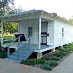 small porch in minimalist mobile home construction with single stairs railing