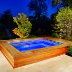 sophisticated built in hot tub design with wooden deck with concrete patio aside greenery