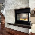 spacious interior decoration idea with white concrete three sided fireplace idea with black hearth and wooden laminated flooring with pendants