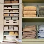 spacious linen closet organizer with small and big slots and drawers and small racks and boxes and towel and slappedn wooden door