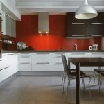 spacious modern kitchen design with red acrylic backsplash idea with white cabinetry and black dining table with white vault pendant and black chairs