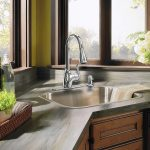 stainless steel sink and best kitchen sink material with modern faucet plus gray countertop plus wooden kitchen cabinets and greenery