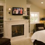 stunning fireplace mantel height in bedroom with plant and flat tv screen plus wall scones on wall decoration above the fireplace and comfy brown armchairs