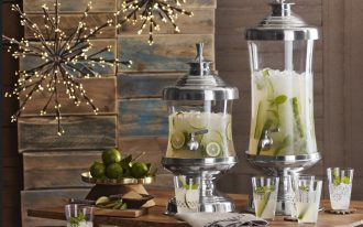 stunning glass beverage dispenser with metal spigot for juice drinks plus lemonade glass and lighting plus limes and silver footed and lid