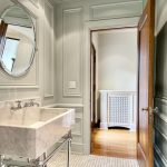 Stunning White Bathroom Idea From Nicole Miller With White Vanity Beneath Round Wall Mirror With Small Tile Flooring Idea
