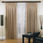 stylish inverted pleat drapes with sheer curtains and standing lamps and black leather armchair and squeare wooden table together with wooden laminate floor